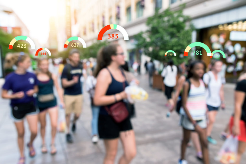 Pedestrians walk in a street with virtual scores hovering over their heads